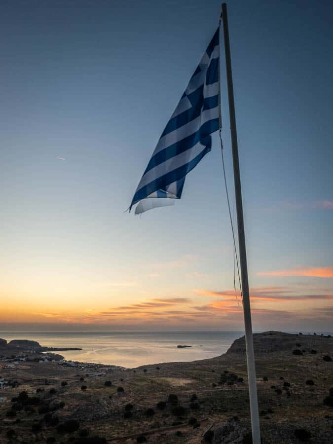Photo of the Greek flag at sunrise at the Prophet Elias church in Pefkos looking towards Lindos