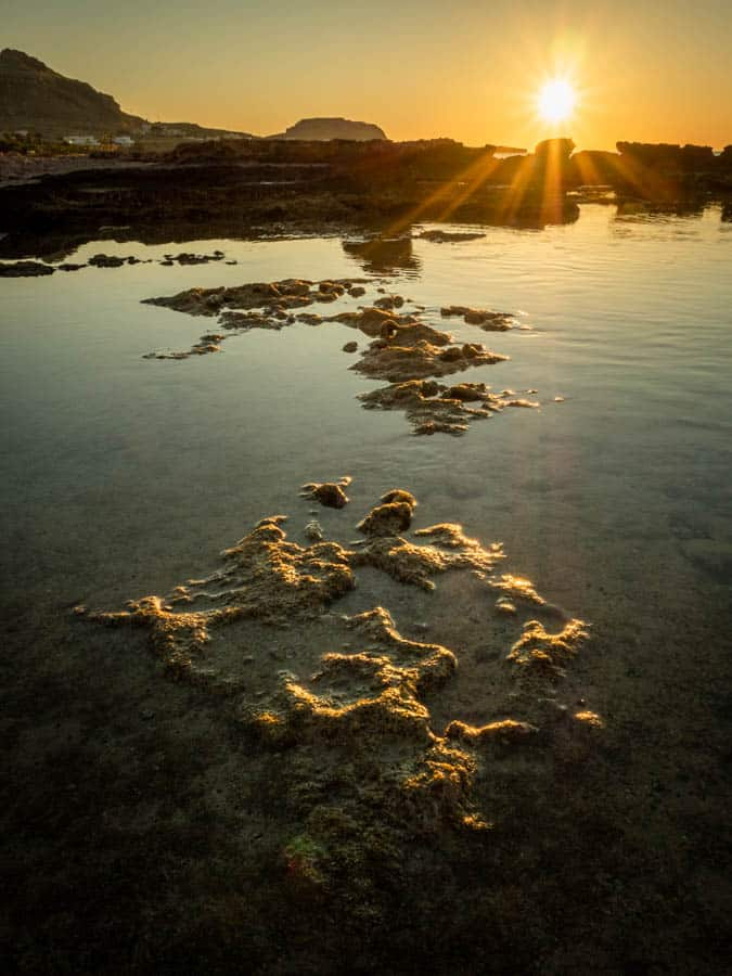 Photo taken at low level of one of the rock pools on the beach at Navarone Bay on the Greek Island of Rhodes with a big bright burst of sunshine. Photo taken with my Olympus OM-D EM5 Mk 2 and 12-40mm F2.8 Pro lens