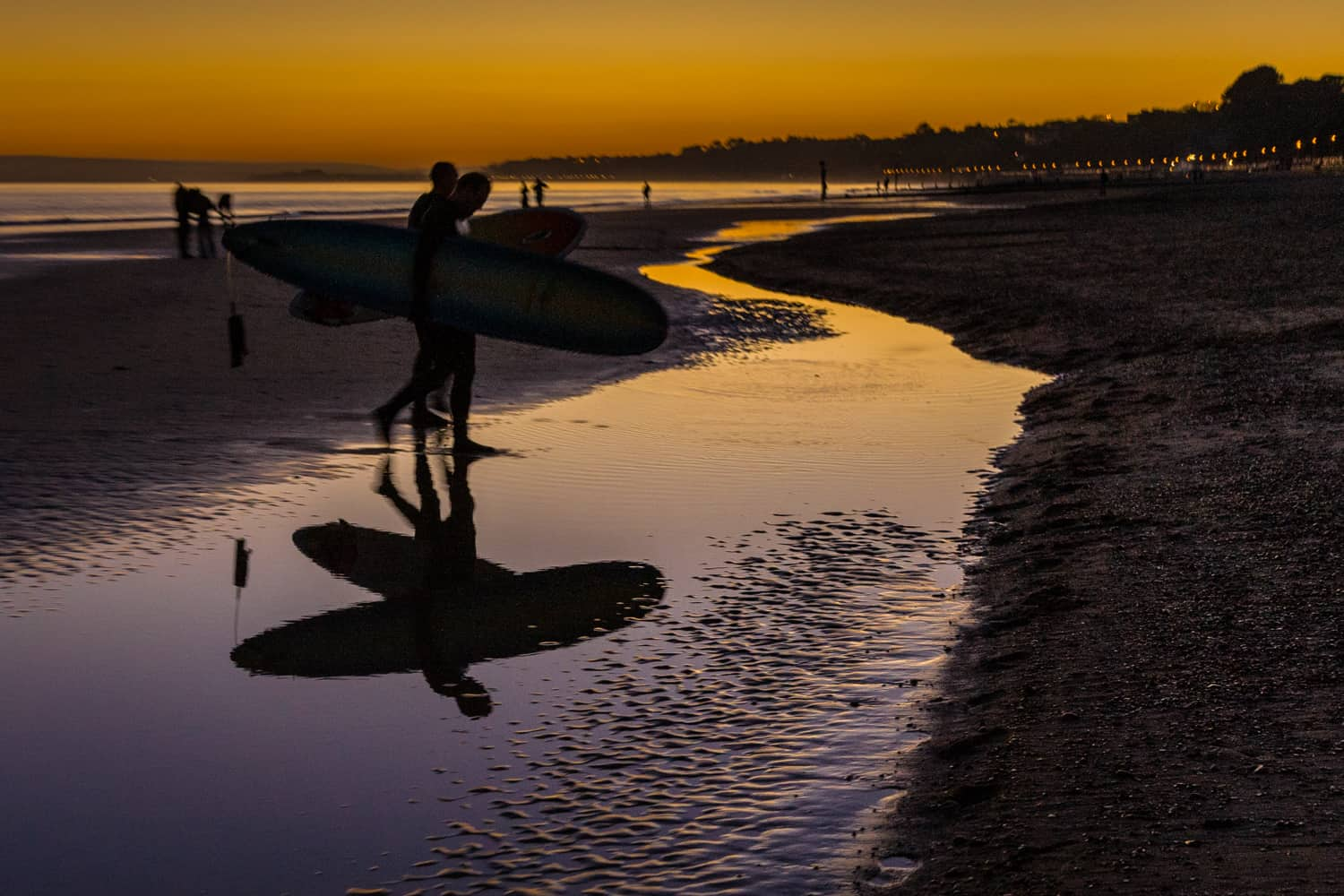 Surfers on Bournemouth Beach at sunset