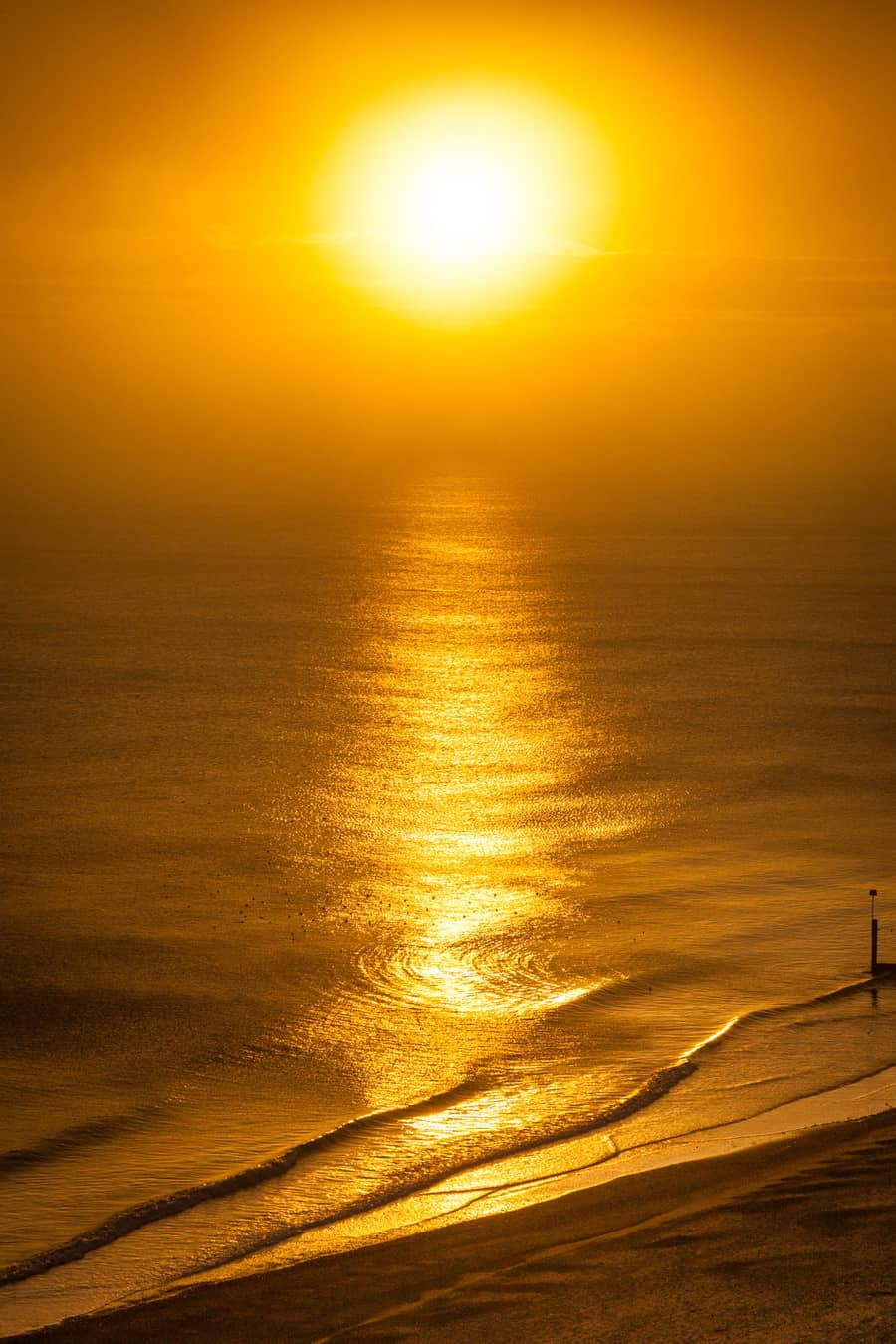 A picture of the sun, sea and beach all illuminated by a lovely bright warm vibrant golden sun