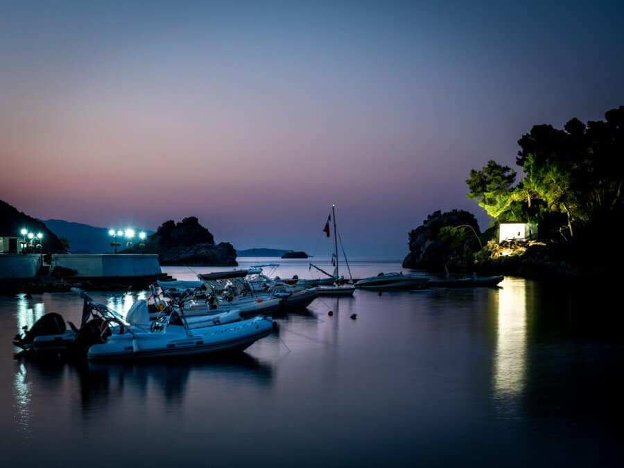 Sunrise view of the boats of Parga and a white building