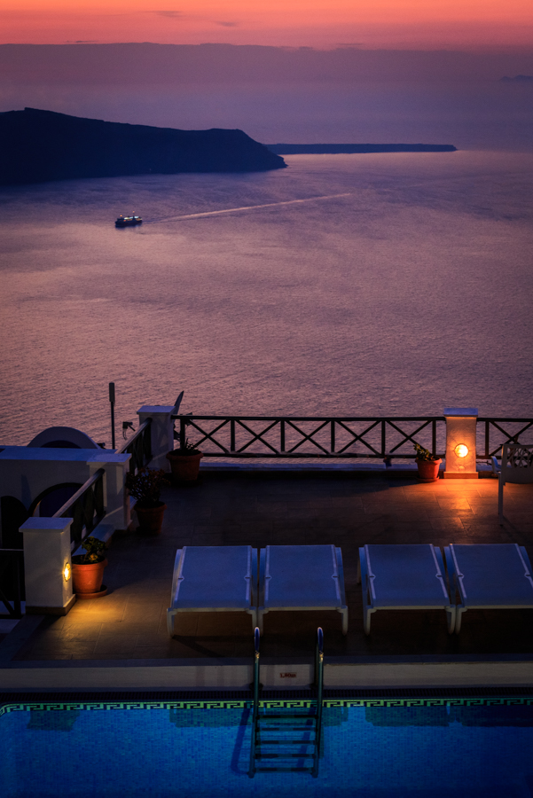 Sunset view of a swimming pool and the amazing sea of Santorini