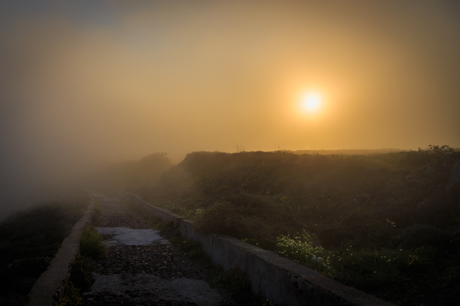 Misty morning path from Imerovigli to Oia at sunrise