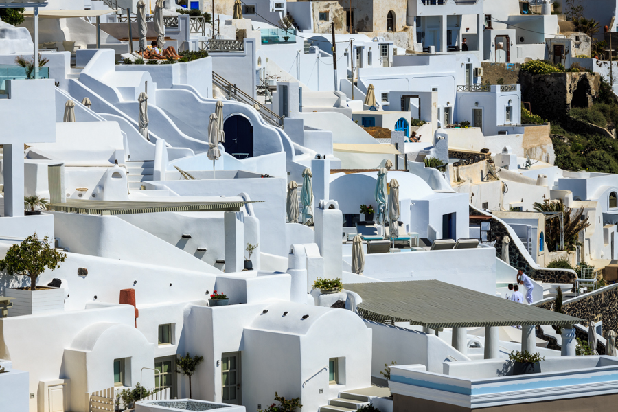 Close up of some of the white buildings of Santorini showing all those closed sun umbrellas